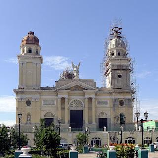 Santiago de Cuba, Catedral de Nuestra Señora de Asunción. Die gelb angestrichene Kathedrale wirkt neoklassizistisch, zwei Türme, der rechte eingerüstet, über dem großen mittleren Tor ein geflügelter Erzengel.