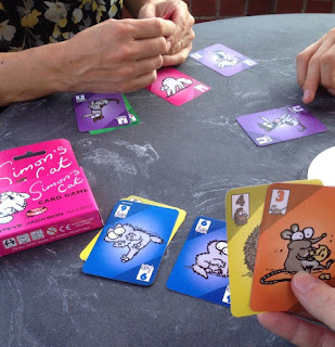 A photo of the hands of three people playing Simon's Cat. The cards in their hands, and on the table, are coloured according to the animal on the card (a cat, a mouse, a kitten, and so forth). Each card is numbered.