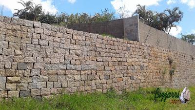 Construção do muro de pedra com pedra tipo pilastra de granito sendo um tipo de muro de pedra com junta seca com concreto e ferragem por trás por se tratar de uma muro de arrimo com pedras, podendo ser com esse tipo de assentamento de pedra ou com as pedras mais encaixadas ou com mais buracos entre as pedras.