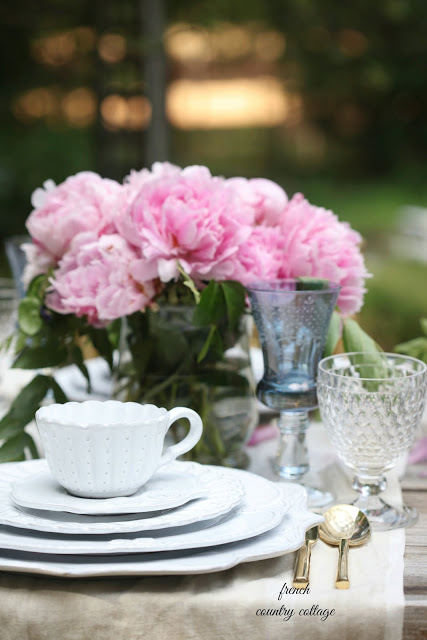 romantic table setting with white dishes outdoors
