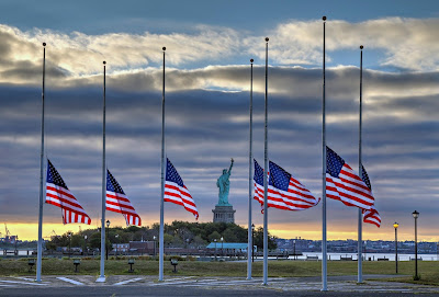 flags at half-mass, in front of Statue of Liberty at sunset