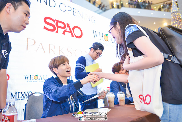 Great smile by LeeTeuk hand shake and pass the autographed cardboard to fans