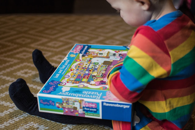 My toddler in a stripy dress holding the jigsaw box which has a picture of the whole puzzle on it