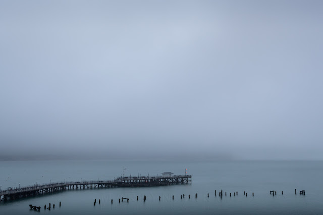 Cliffs obscured by sea mist with Swanage piers in the foreground