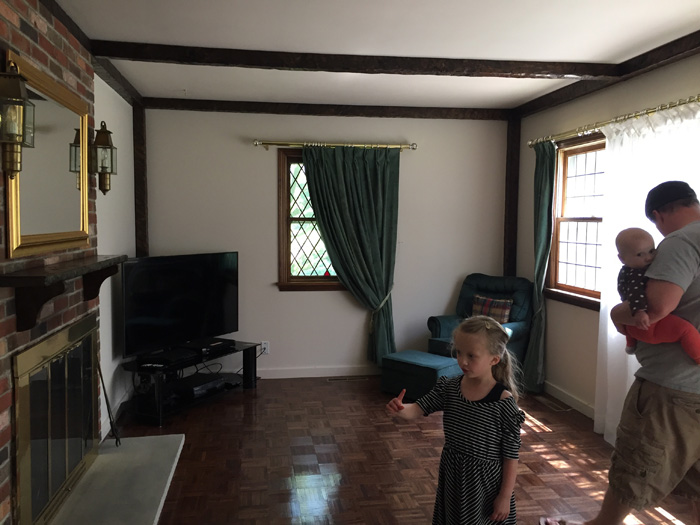 1970's family room with parquet floors and dark wood beams on ceiling