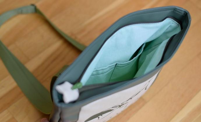 Blick durch den Reißverschluss ins Innere der Tasche: pastellgrüne Baumwolle und ein unterteiltes, aufgesetztes Fach ohne Verschluss