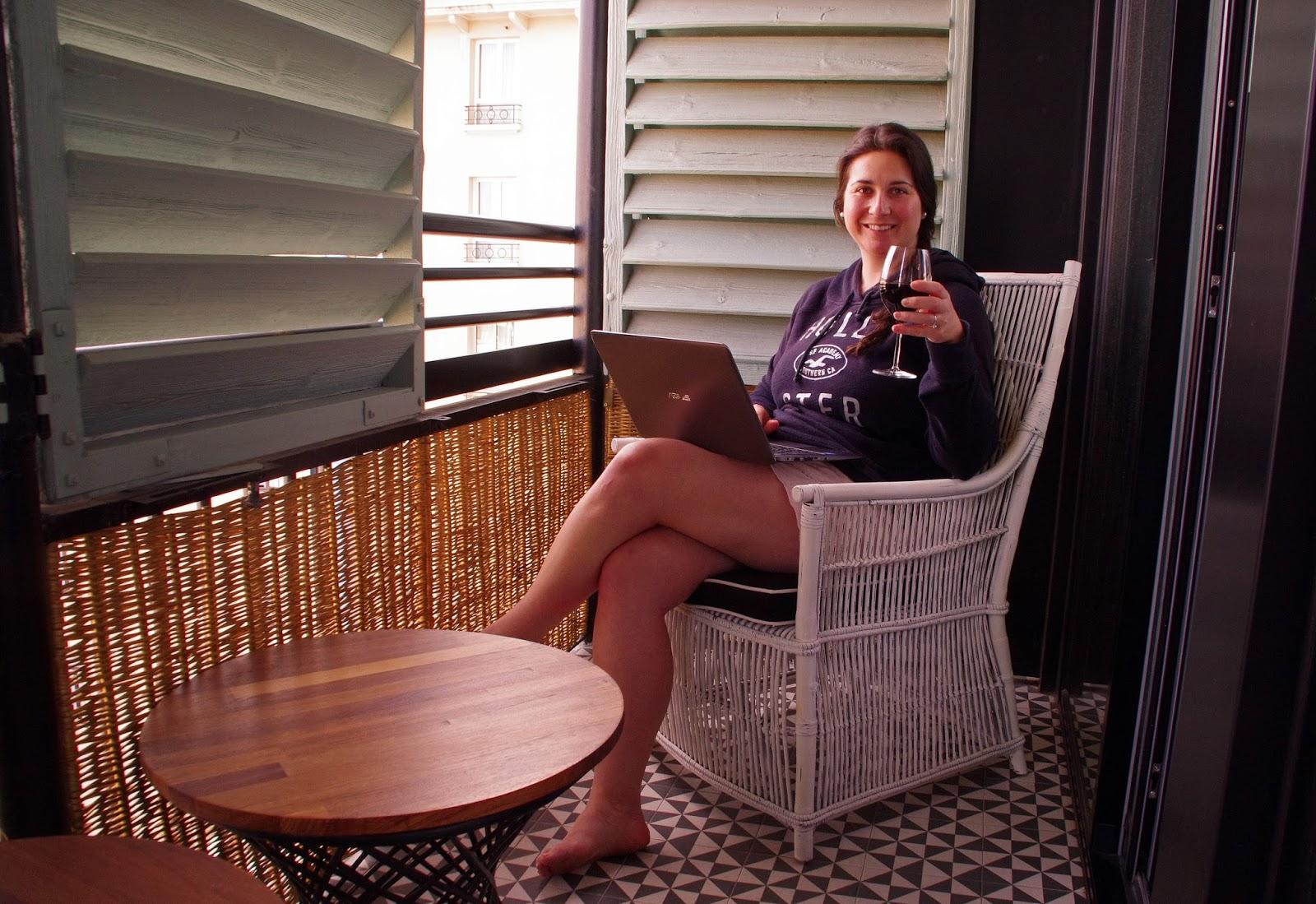 Simone drinking wine on balcony at Cotton House Hotel Barcelona
