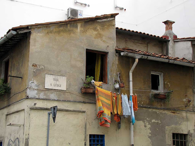Laundry hanging from a clothesline out of a window in via San Luigi, Livorno