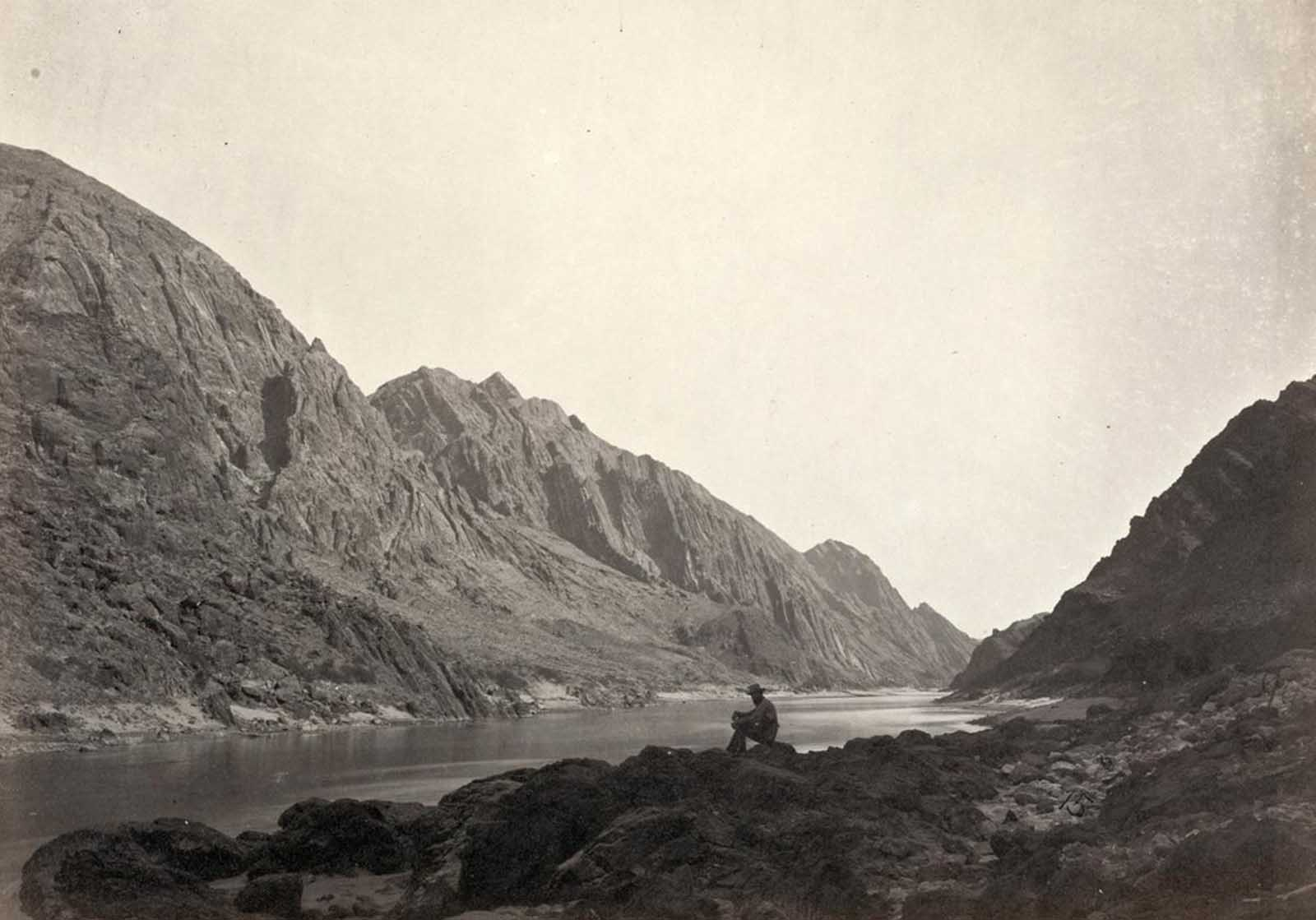 A man sits on a rocky shore beside the Colorado River in Iceberg Canyon, on the border of Mojave County, Arizona, and Clark County, Nevada in 1871.
