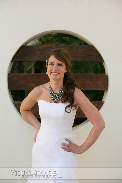 Bride striking a pose in front of wall with circle