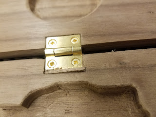 brass hinge and wooden shim in carved box inset