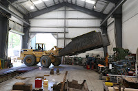 Large loader lifts new tender tank from floor in Conservation and Restoration Center.