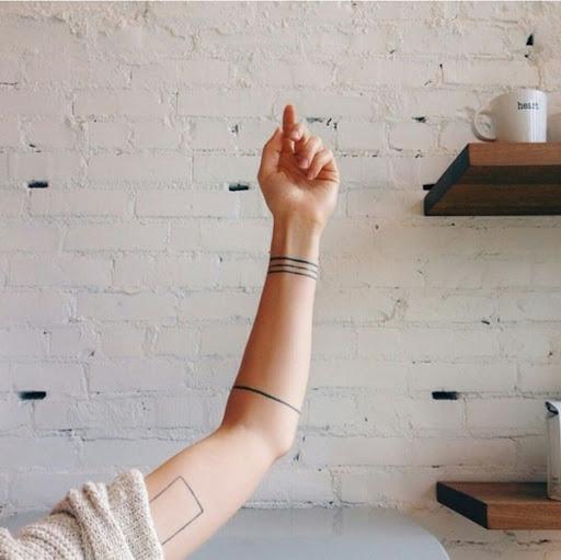 Três linhas pretas funcionam como uma pulseira, enquanto uma única linha preta funciona como um antebraço banda neste tatuagem conjunto.