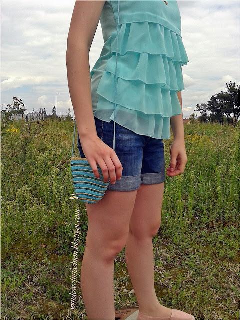 Miętowa bluzka z falbankami, jeansowe krótkie spodenki, espadryle, słomkowo-cekinowa mini torebka