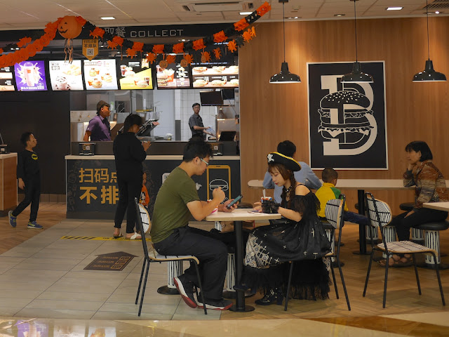 young woman wearing a pirate hat sitting at McDonald's in Zhongshan, China