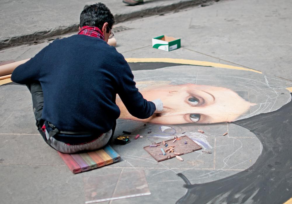 Un homme dessine à la craie sur un trottoir une reproduction d'une oeuvre célèbre