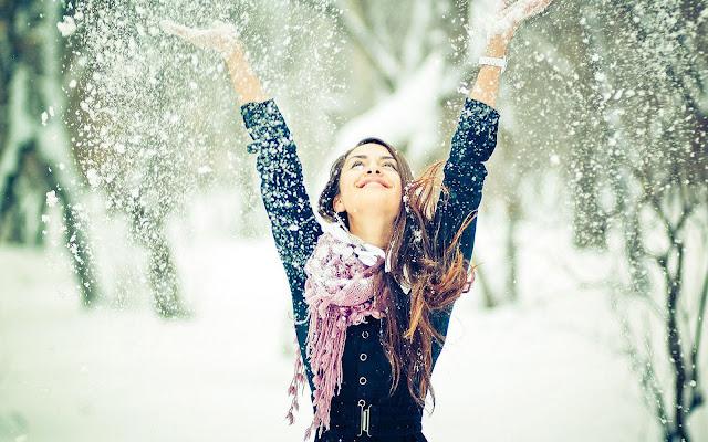 Vrouw gooit sneeuw in de lucht van blijdschap