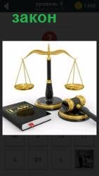 Весы и закон на весах правосудия. Рядом лежат молоток и подставка для него