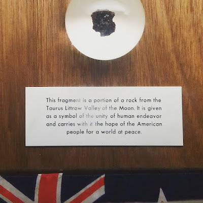 Piece of rock on a wall plaque. Underneath it is a sign saying'This fragment is a portion of a rock from the Tourus Littrow Valley of th eMoon. It is given as a symbol of the unity of human endeavor and carries with it the hope of the American people for a world of peace. Under the sign is a New Zealand flag.