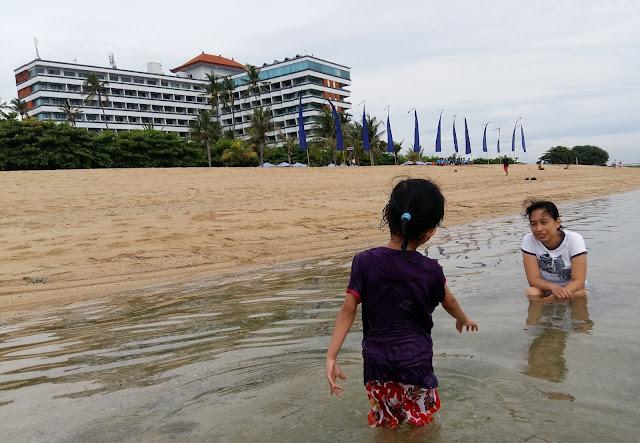 Dea dan mamanya main air di pantai.