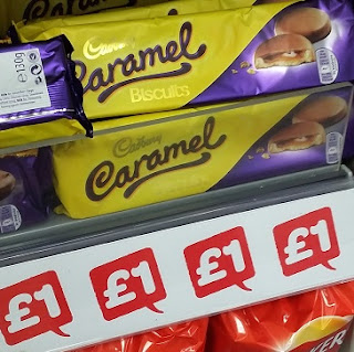 Picture of packets of Cadbury's Caramel Biscuits on a shelf, on offer at £1 for 130g.