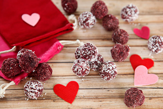 Red truffle dog treats on a table with pink and red hearts and drawstring treat bags