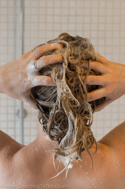 A view of the back of a woman's head while she washes her hair in the shower