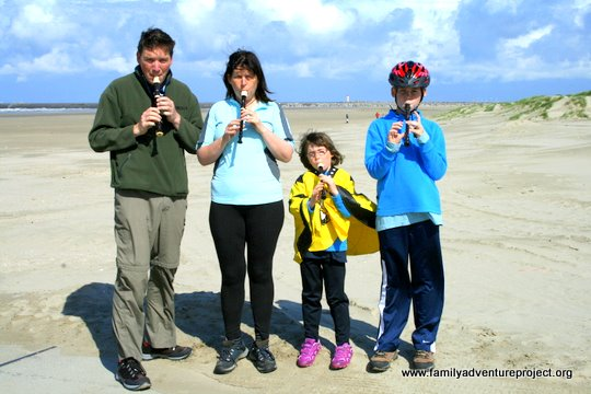 Family plays recorder on beach