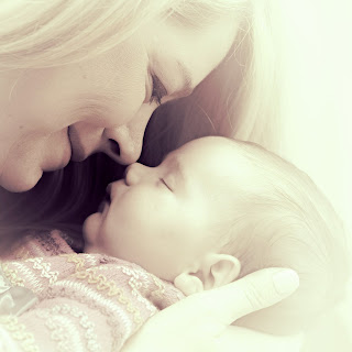 A mother holding her baby looking into her face with noses touching