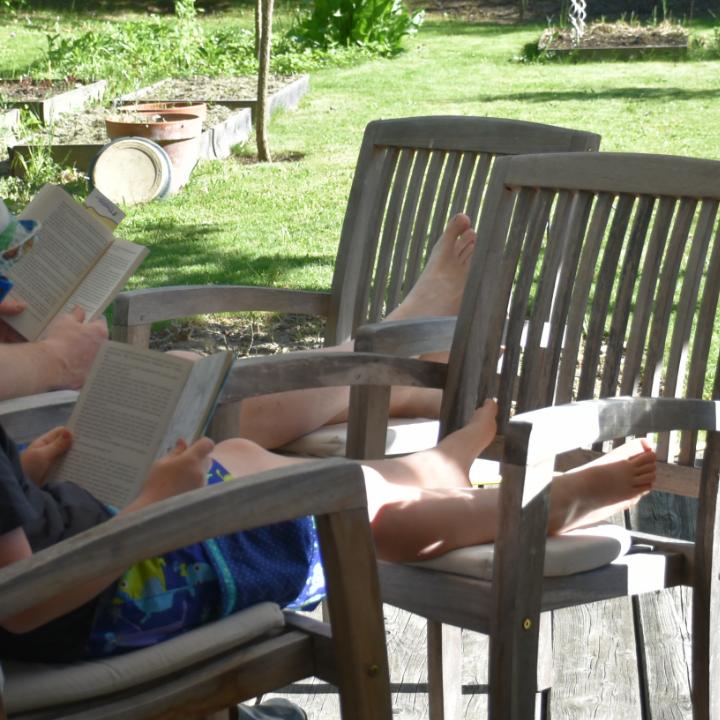 Vater und Sohn lesen im Garten ein Buch