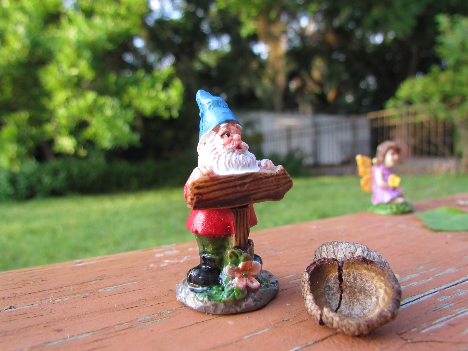 A Gnome Holding a Sign in the Garden + Garden Gnome and Fairy Statue at Magic Hour Photography
