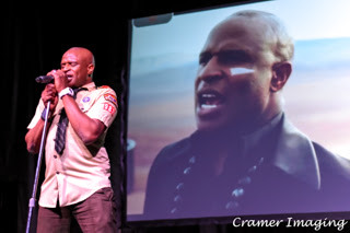Cramer Imaging's professional quality concert photograph of singer Alex Boyé in scout uniform in person and on screen in Firth Idaho