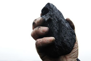 A coal merchant holds up a lump of coal for the camera in his yard in Melmerby, northern England November 5, 2008. (Credit: Reuters/Nigel) Click to Enlarge.