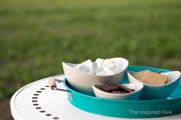 Tips for hosting a summer BBQ party. Put smores ingredients in bowls on a tray. Easy to carry everything outside when the fire is ready!