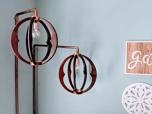 Copper and wood pendant lights with copper pipes attached to wall
