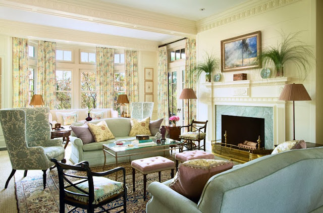 Living room in a South Carolina estate with light blue dueling sofa, a blue and white arm chair and lavender upholstered ottomans