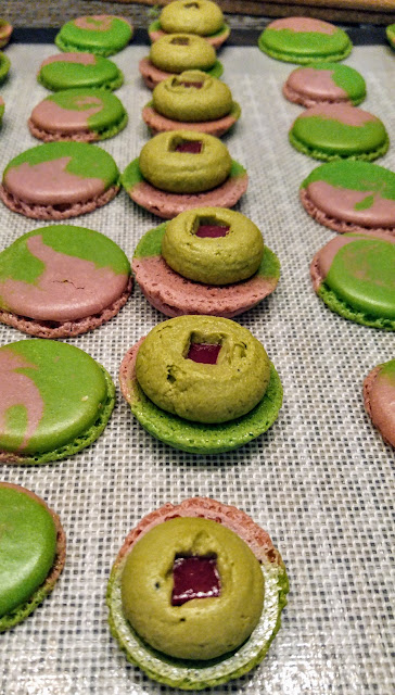 A tray of raspberry matcha macarons with tops separated and raspberry jellies inserted into each filling.