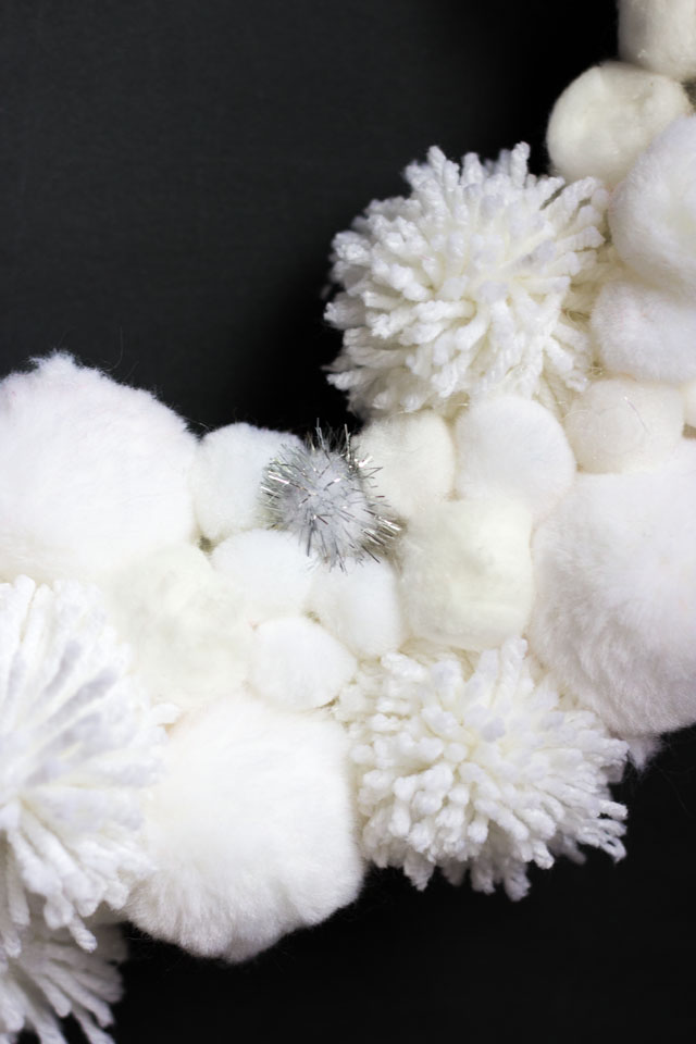 Love this DIY winter wreath bursting with pom-pom snowballs!
