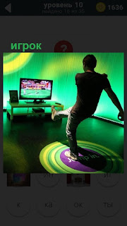 В комнате перед телевизором стоит парень игрок , подняв одну ногу