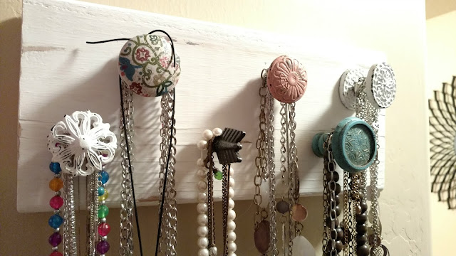 Make your own hanging necklace holder using a piece of scrap wood and some cute drawer knobs!