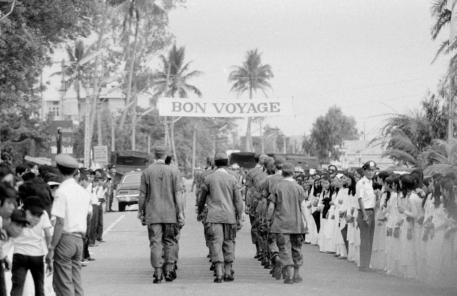 A bon voyage banner stretches overhead in Da Nang, South Vietnam, as soldiers march down a street following a farewell ceremony for some of the last U.S. troops in the country's northern military region, on March 26, 1973.