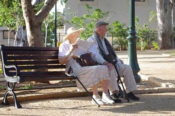 Imagem de um casal de idosos sentados na praça, um lendo e o outro observando a Natureza