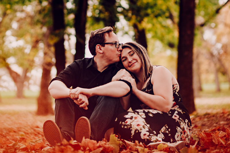 couple sitting in fall leaves