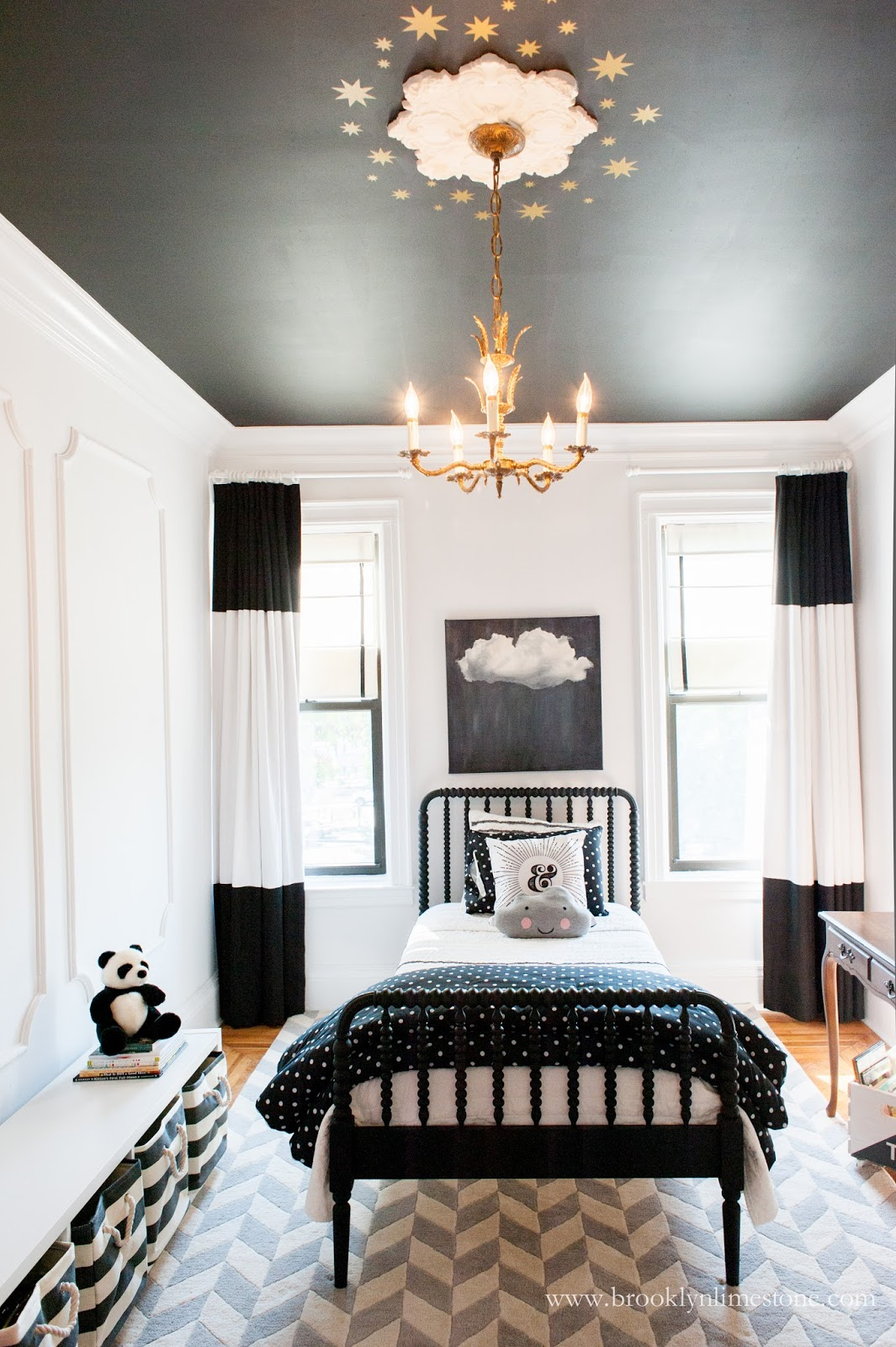 Girl's bedroom with black ceiling, white walls, black and white drapes
