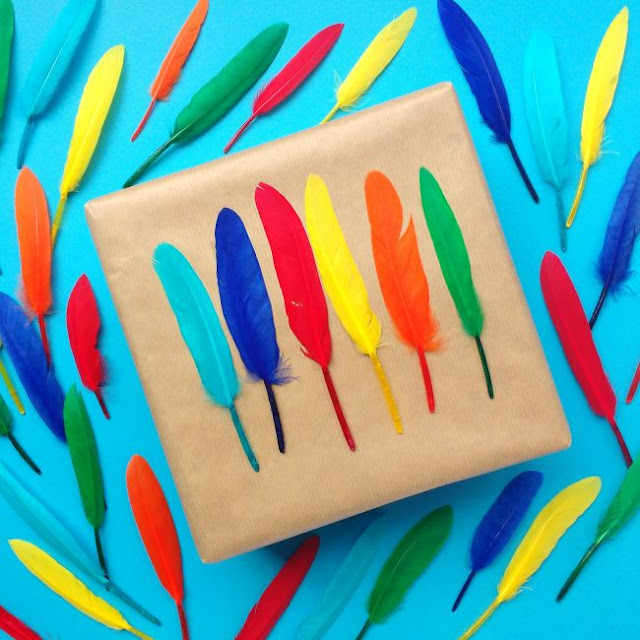 parcel decorated with colourful craft feathers
