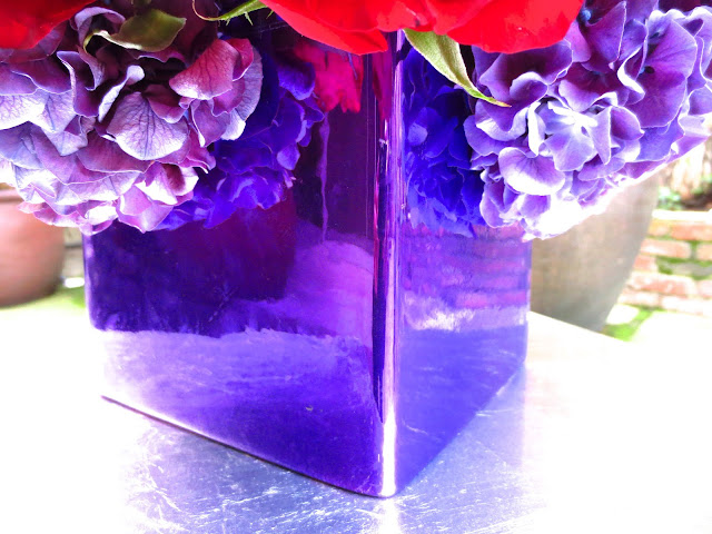 close up of square metallic ceramic vase holding a rose, hydrangea and orchid flower arrangement on a patio table