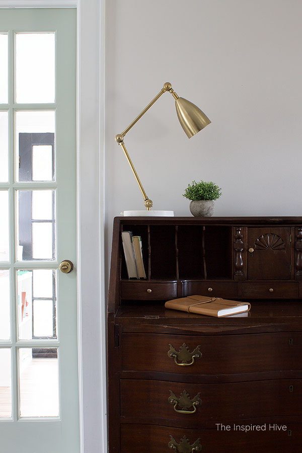 Antique secretary desk with brass hardware, brass and marble task lamp, and green painted french door