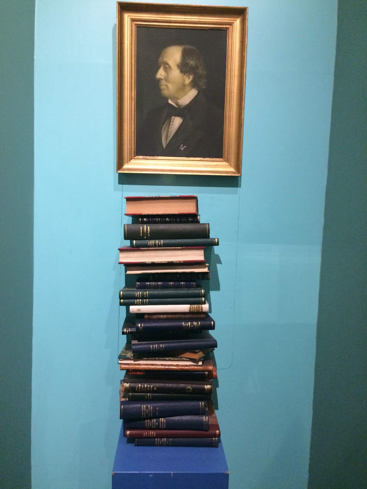 Portrait of Hans Christian Andersen above a stack of old editions of his fairy tales in Danish
