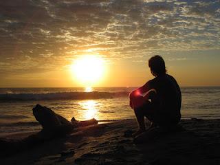 Silueta de un hombre sentado en la playa, mirando al atardecer.