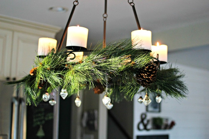Candle chandelier with greenery and mercury glass ornaments as holiday decor - www.goldenboysandme.com